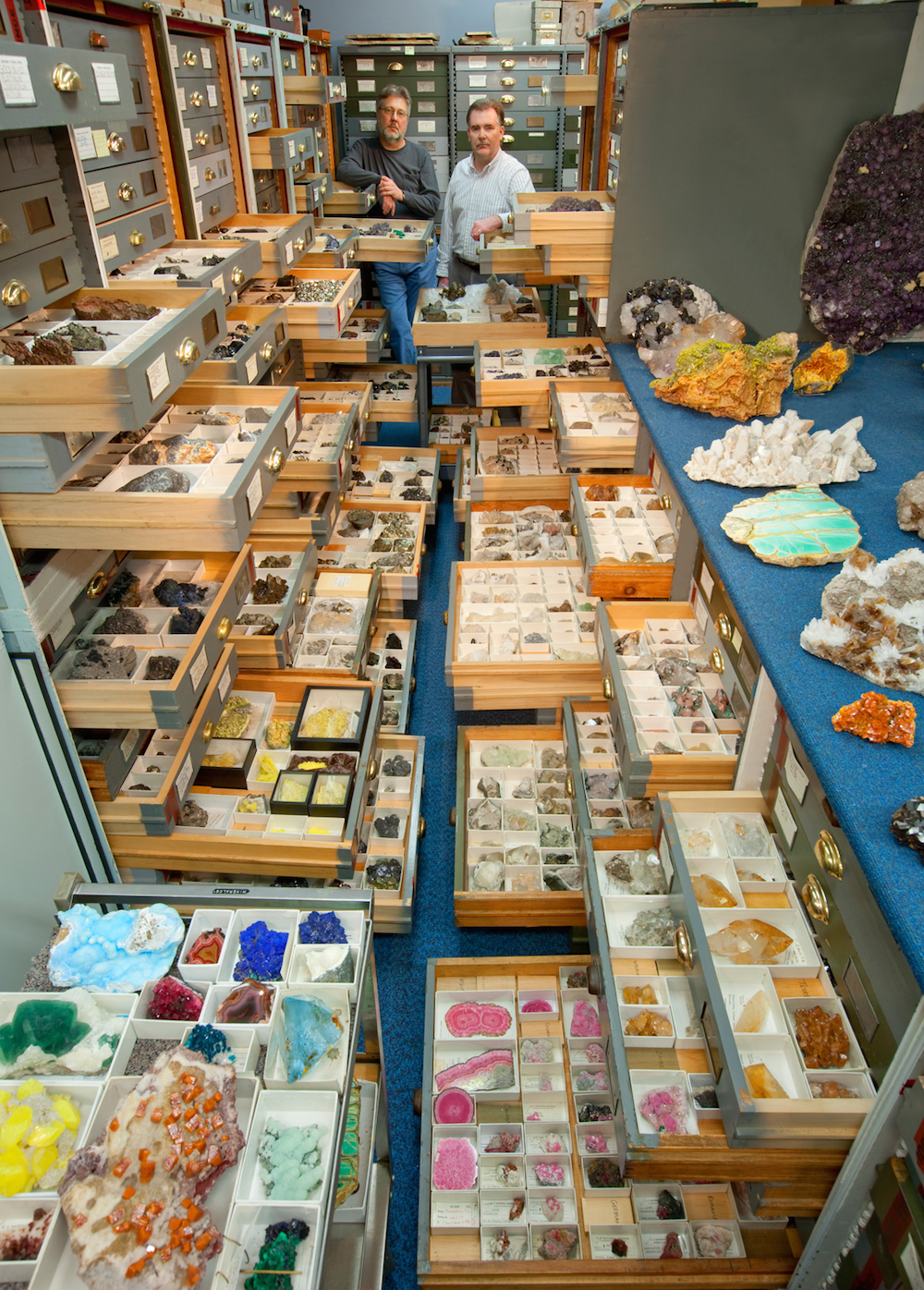 """An assortment of mineral specimens from the Department of Mineral Sciences' collections are displayed in the storage vault known as the """"Blue Room,"""" at the Smithsonian Institution's National Museum of Natural History. Mineral Sciences staff present are (left) Paul Pohwat, Collections Manager of Minerals, and (right) Russell Feather, Collections Manager of Gems."""