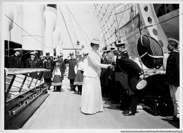 Императрицу Александру Фёдоровну приветствуют на борту императорской яхты.На заднем плане её молодые дочери приветствуют экипаж