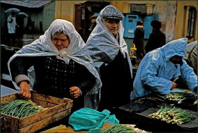 Торговцы на рынке, укрытые от дождя