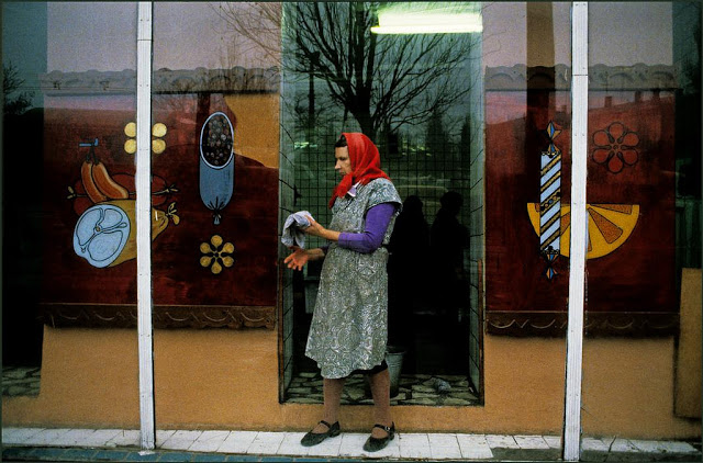 Женщина чистит витрину продуктового магазина