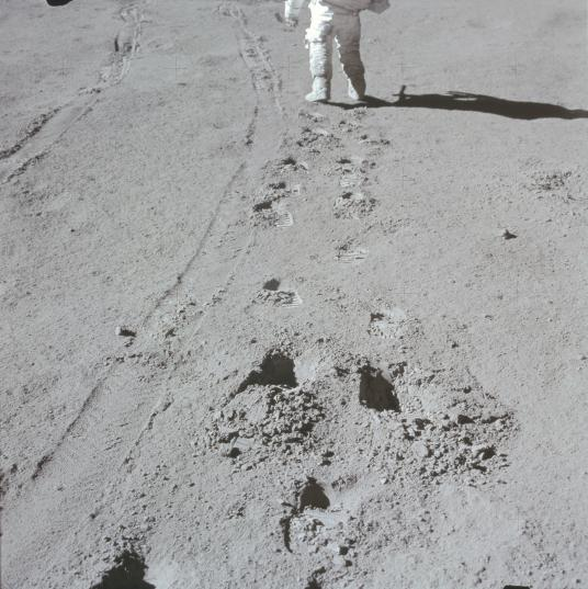 Член экипажа Аполлона-15 ходит рядом со следами, оставленными лунноходом, 1971 год
