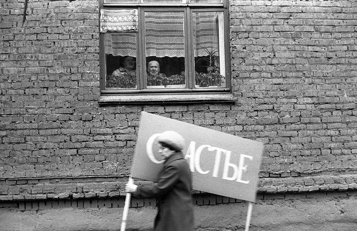 Женщина с плакатом спешит на первомайскую демонстрацию, 1983 год