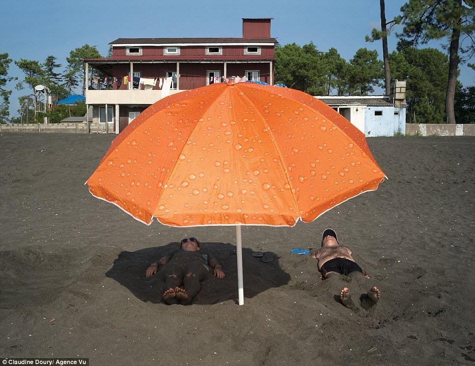 Гости санатория принимают солнечные ванны в магнитном песке. Считается, что он облегчает различные заболевания, связанные с сердцем, суставами, кровообращением и костями
