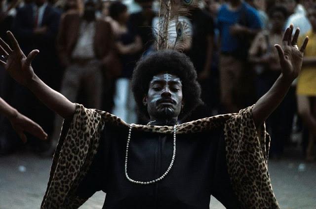 Мужчина в перьях и чёрном бубу танцует на улице
