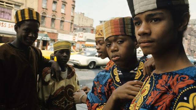 Группа ребят в разноцветных головных уборах и туниках на улице Гарлема