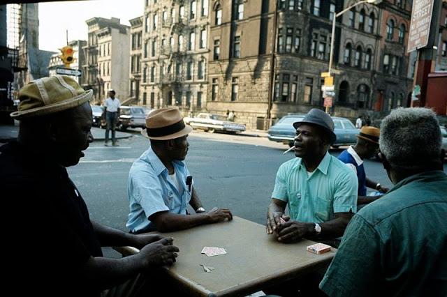 Мужчины играют в карты на тротуаре