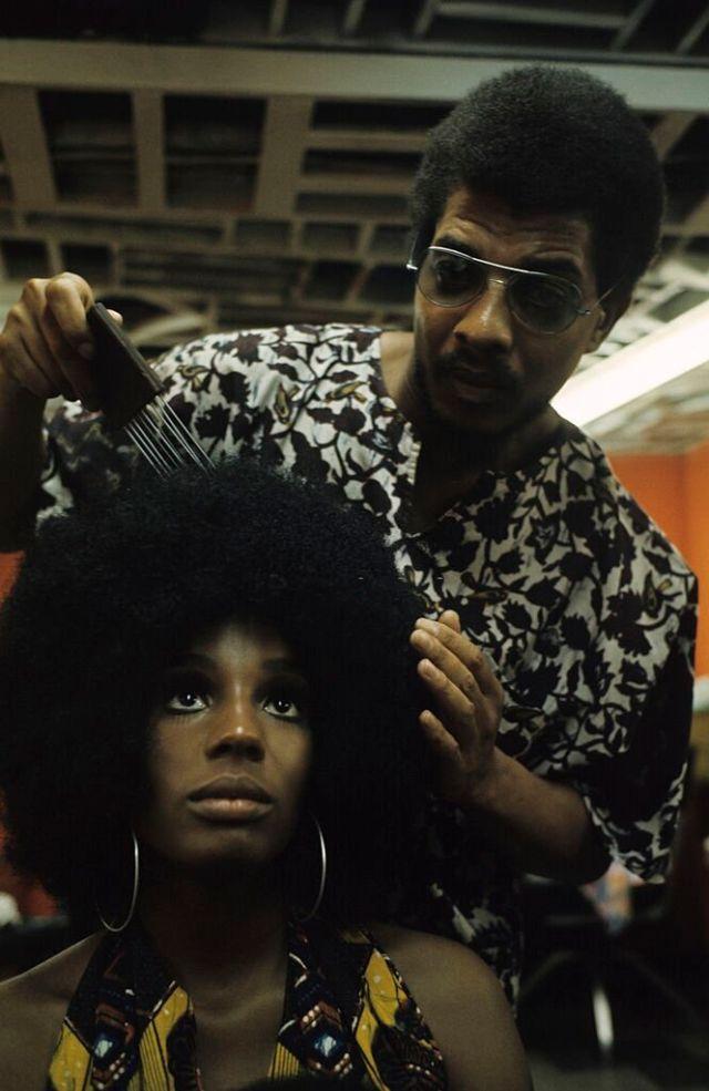 Парикмахер расчёсывает модную причёску своей клиентки