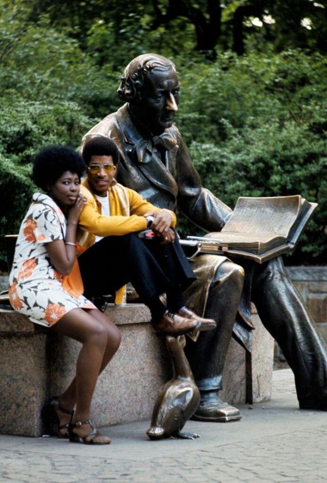 Пара сидит рядом со статуей