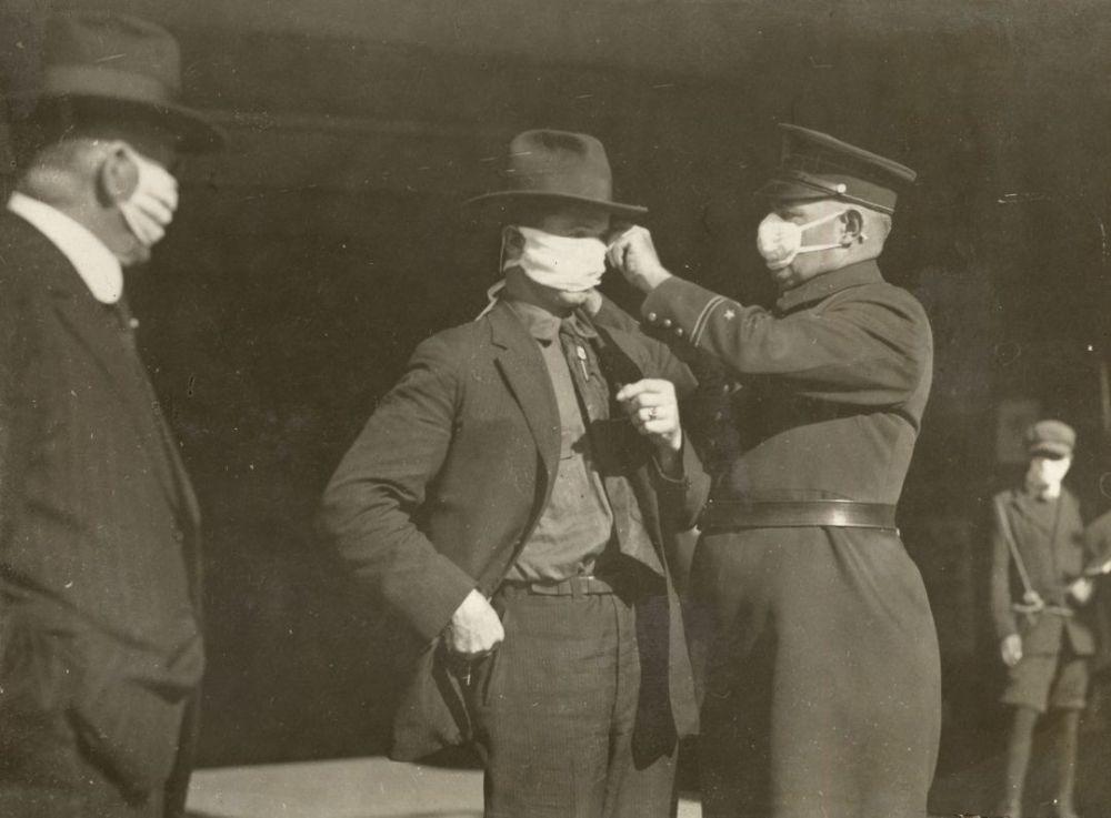 Полицейский поправляет мужчине маску