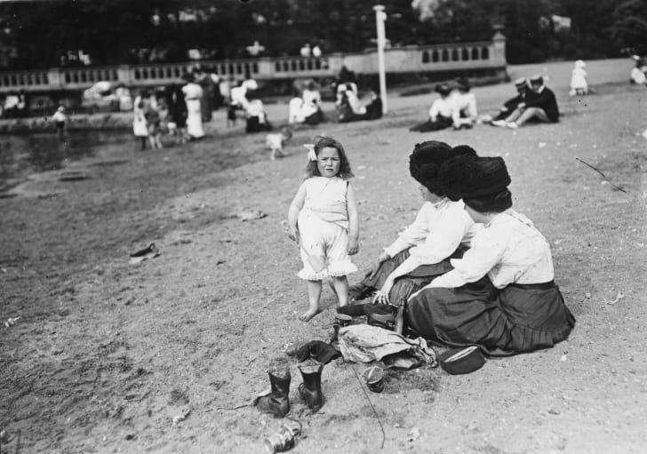 1911 год: ребёнок играет с лопатой в песке, пока её мама и тётя наблюдают за ней. Фулхэм, Лондон