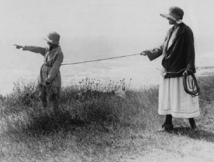 1925 год: женщина крепко держит верёвку, обвязанную вокруг талии дочери, во время прогулки по вершине утеса