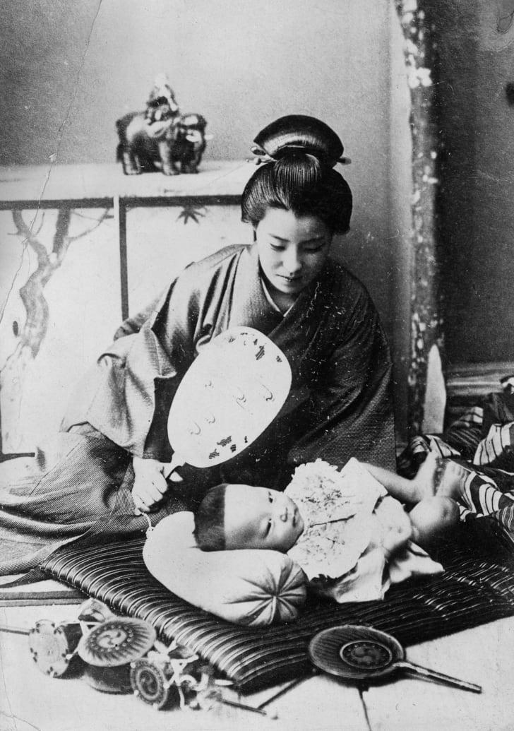 1930 год: мама обмахивает своего ребёнка, лежащего на полу