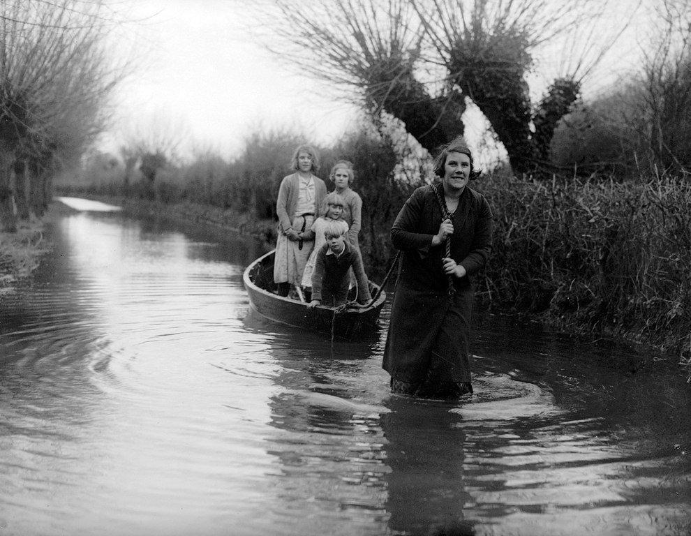 1935 год: мама буксирует своих детей в школу в Берроубридж, Англия, во время сильного наводнения
