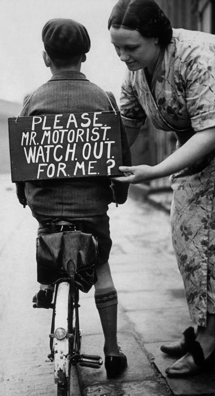 1937 год: мама прикрепляет к спине сына табличку с надписью «Пожалуйста, мистер автомобилист, берегись меня», прежде чем он отправится в поездку на велосипеде