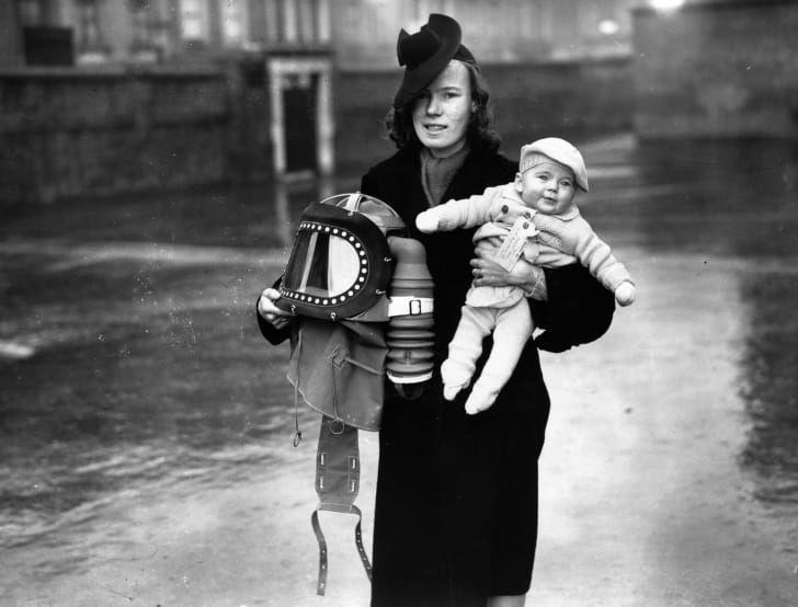 Мать несёт противогаз, созданный специально для младенцев
