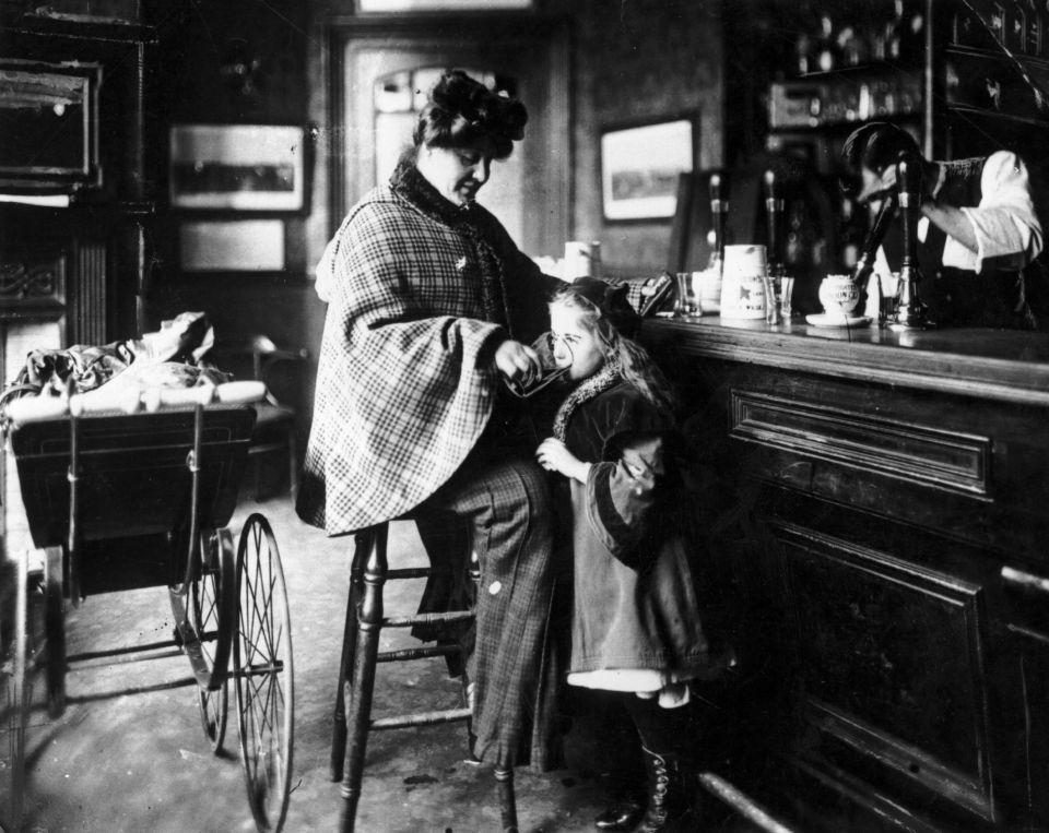 1900 год: мать даёт дочери выпить в баре, в то время как другой ребёнок спит в коляске рядом с ней