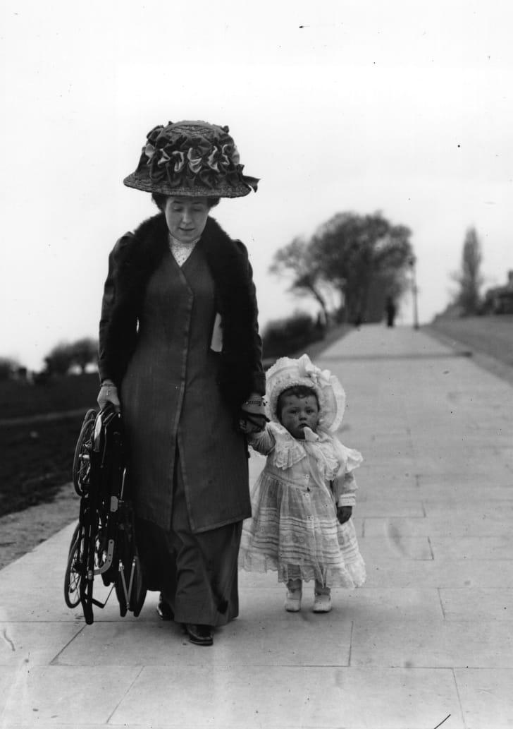 1910 год: мать идёт со своим младенцем и держит в руке новую детскую коляску Sturgis