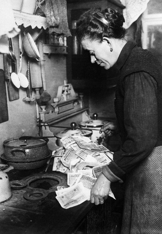 Женщина использует банкноты, чтобы разжечь свою плиту, 1923 год
