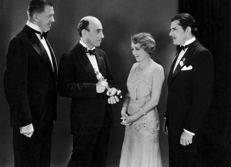 Президент Академии кинематографических искусств и наук Уильям Демилль вручает «Оскара» Мэри Пикфорд (в окружении Уорнера Бакстера и Ханса Крали) на 2-й церемонии в 1930 году