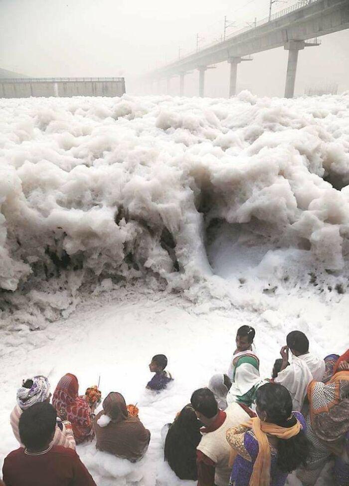 Люди возносят молитвы у реки Ямуна, Индия, которая вспенивается из промышленных отходов