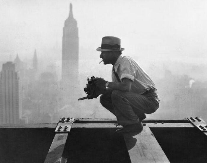 Чарльз Эббетс фотографирует «Обед на небоскрёбе», знаменитую фотографию рабочих в Нью-Йорке, которые едят свой обед на висящей стальной балке